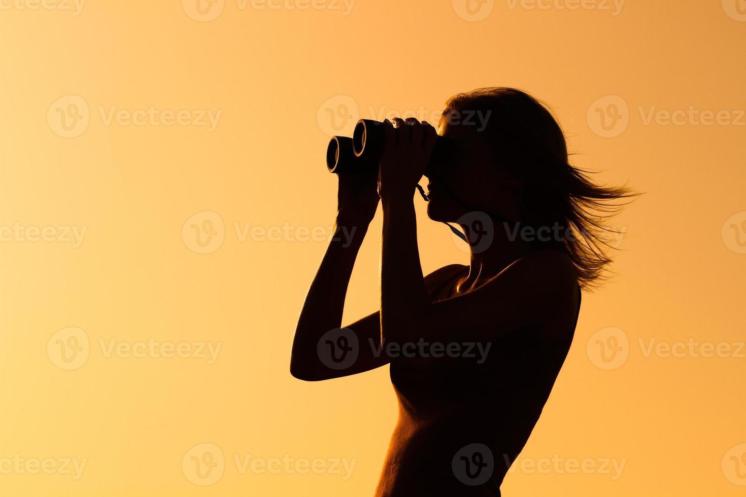 Genießen Sie bei Sonnenuntergang mit einem Fernglas foto
