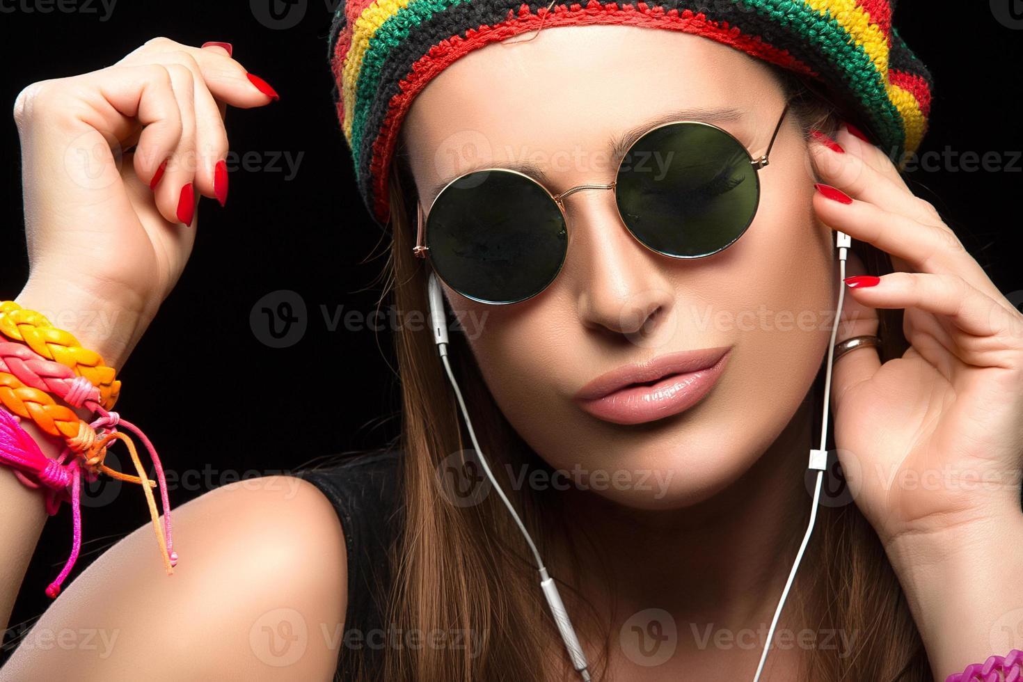 modische junge Frau, die Musik durch Kopfhörer genießt foto
