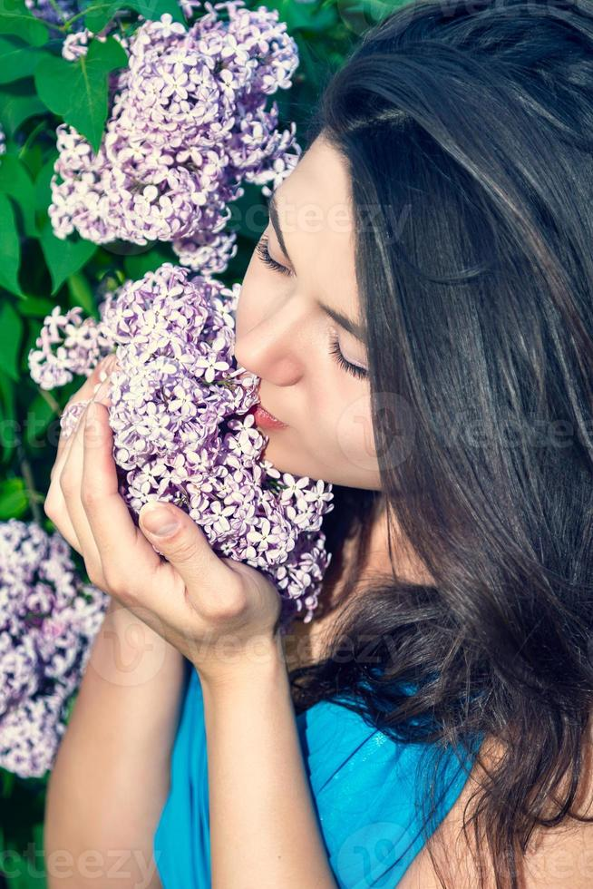 schöne Frau, die den Geruch von Blumen genießt foto