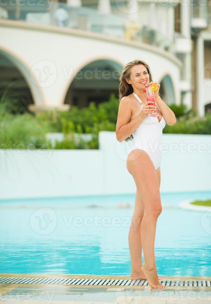 glückliche junge Frau, die Cocktail am Pool genießt foto
