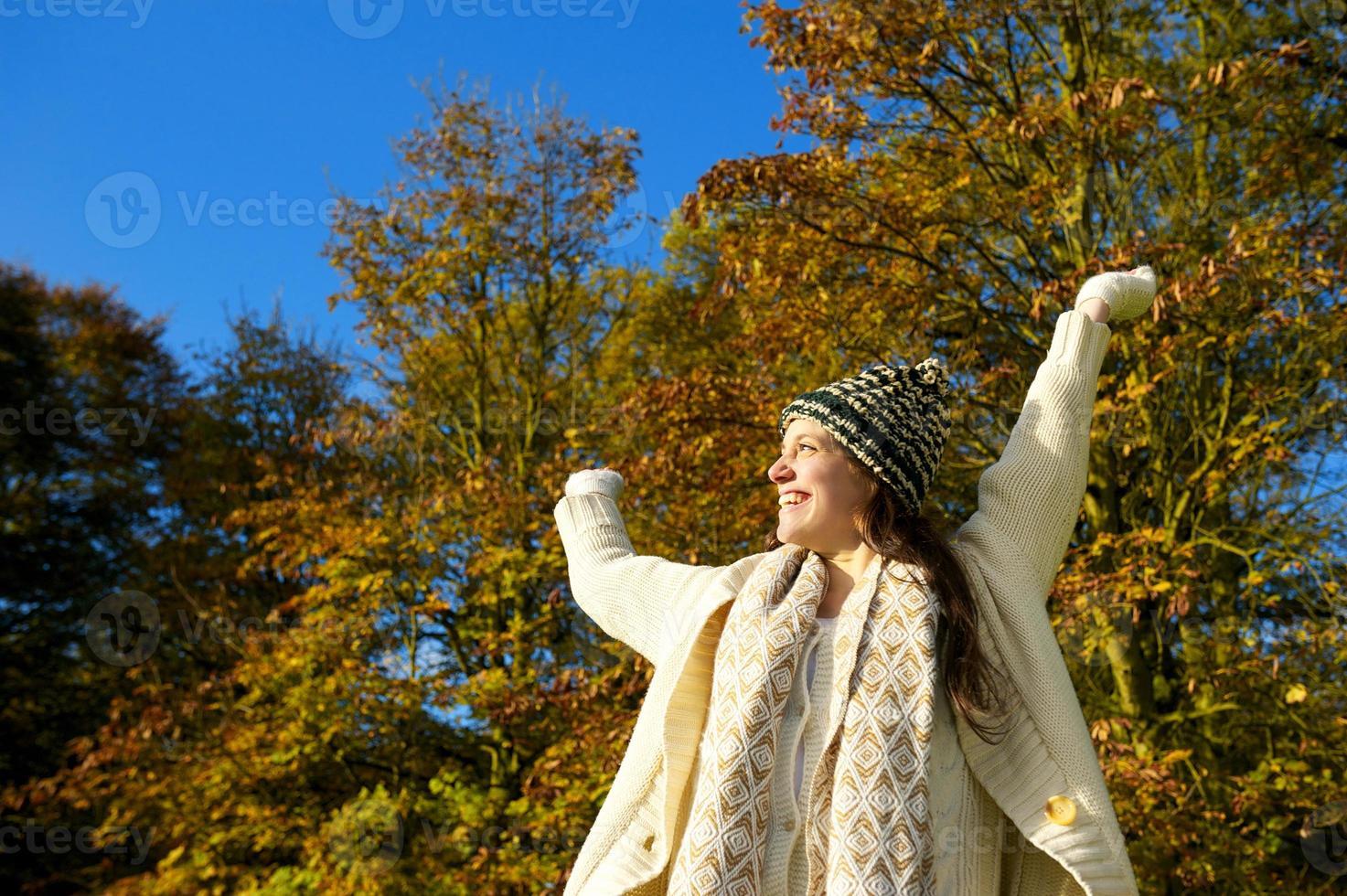 glückliche Frau, die lächelt und einen Herbsttag im Freien genießt foto