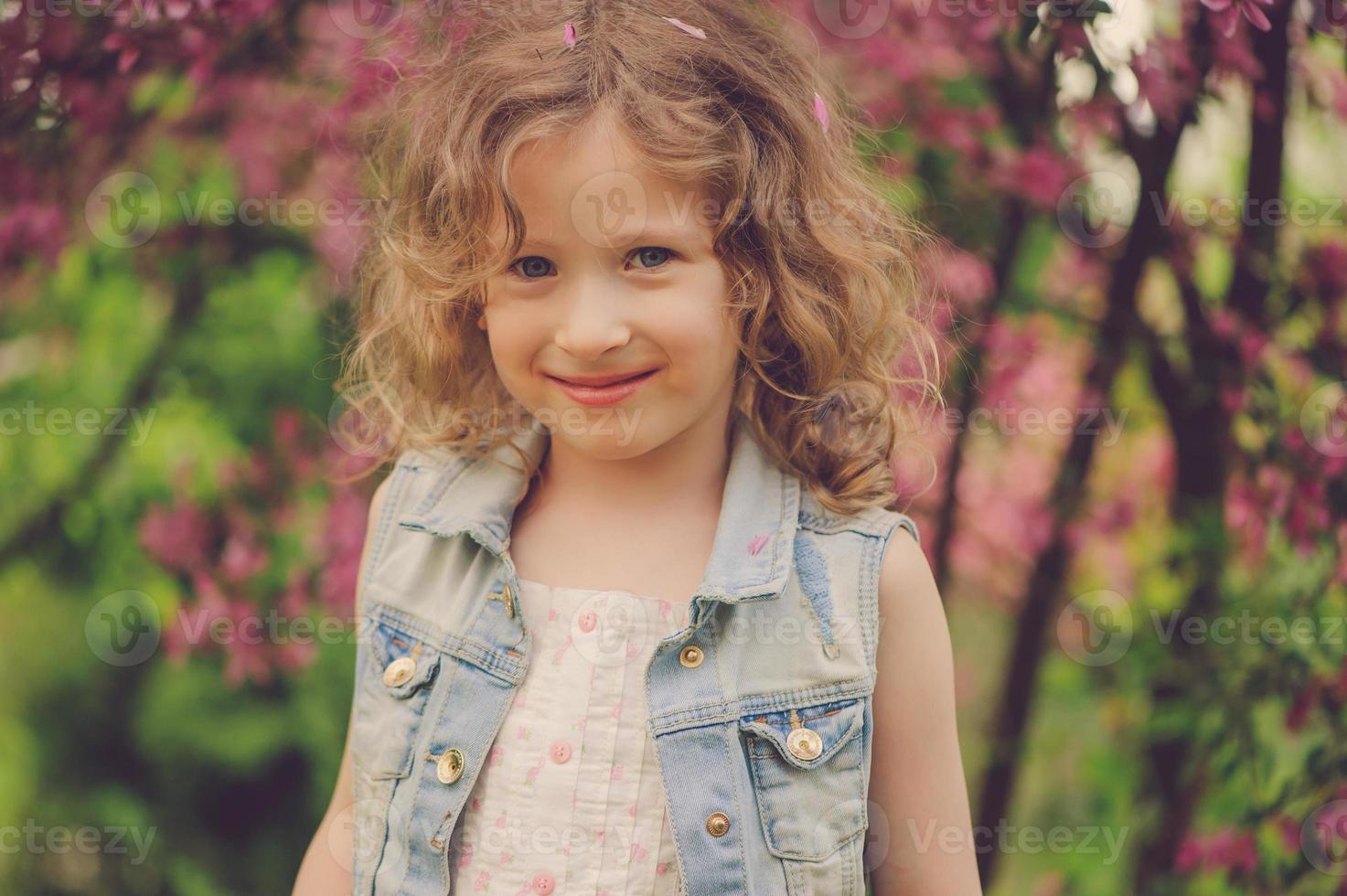 niedliches Kindermädchen, das Frühling im gemütlichen Landgarten genießt foto
