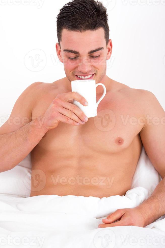 gutaussehender Mann im Bett genießt den Geruch von Kaffee foto