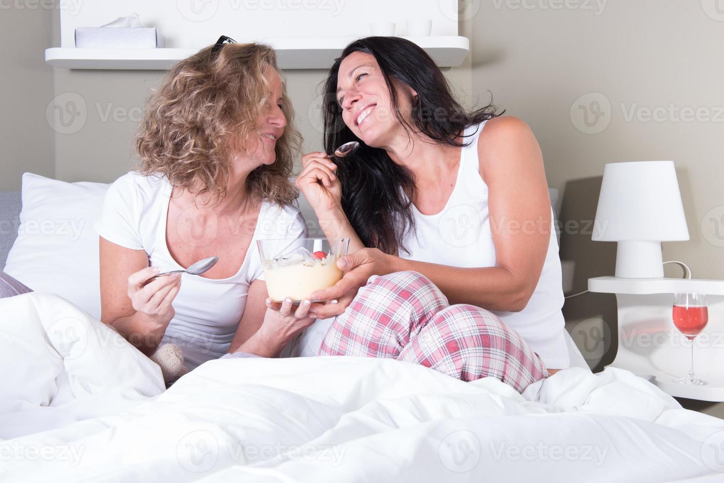 zwei attraktive Frauen genießen ihren Frauenabend im Bett foto