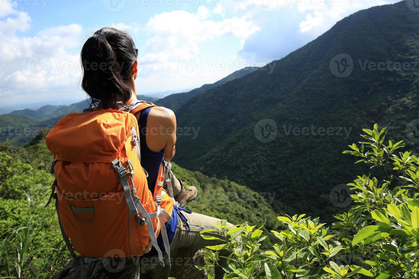 Frau Backpacker genießen Sie die Aussicht auf Berggipfel Klippe foto