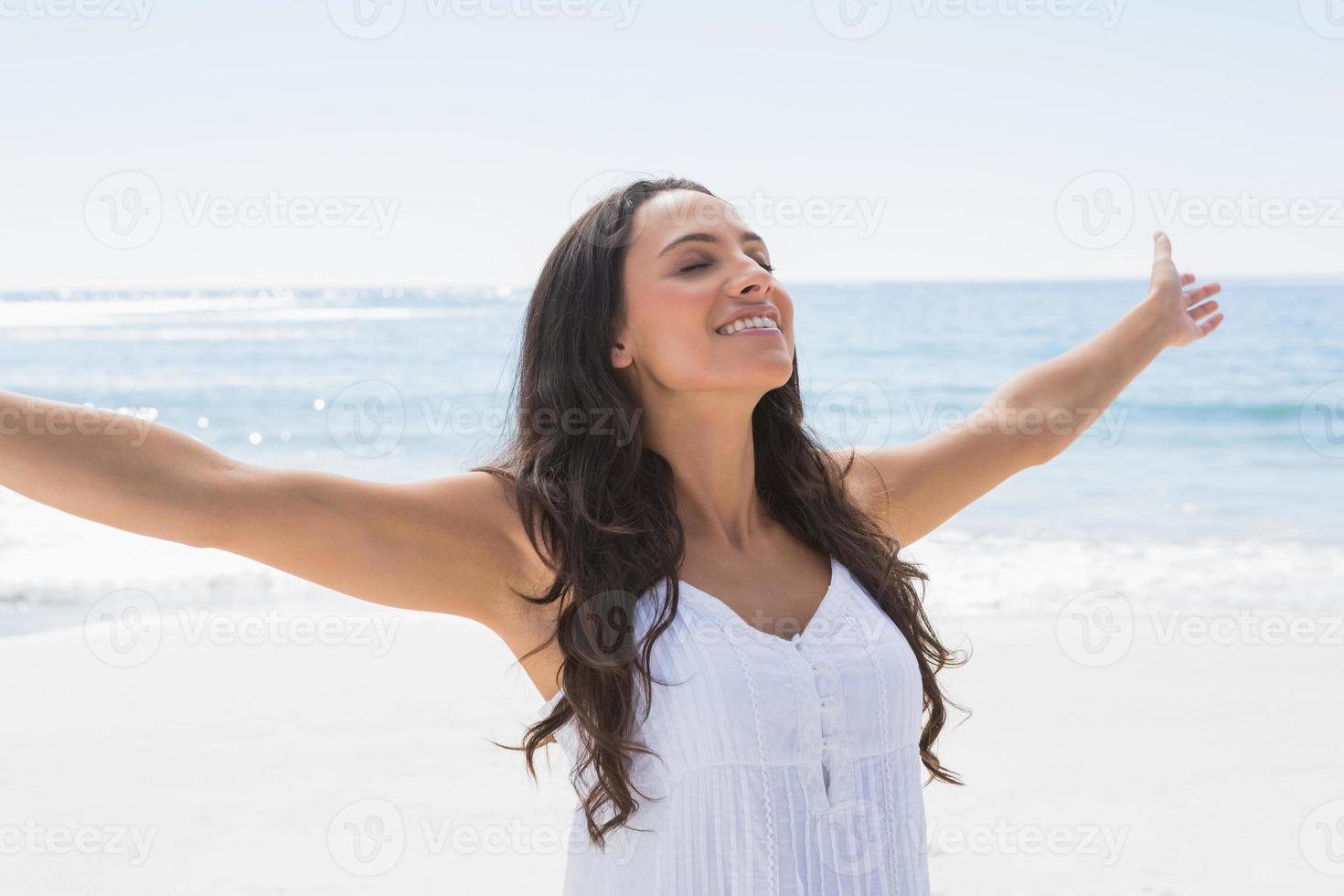 schöne Brünette im weißen Sonnenkleid, das die Sonne genießt foto