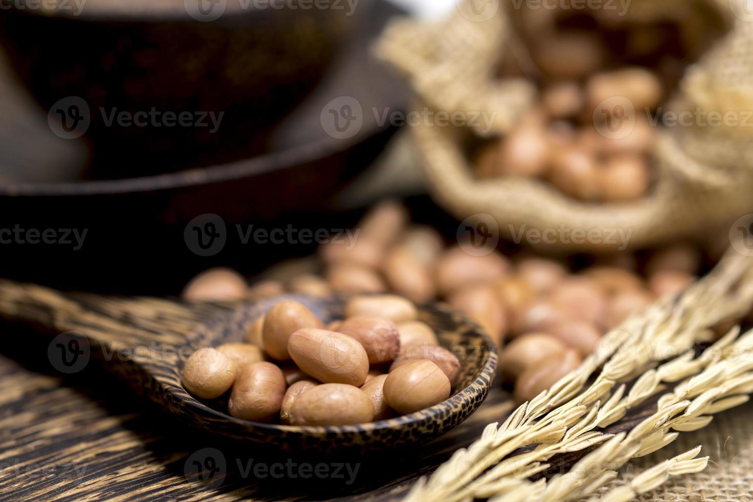 Keine Schale trockene Erdnuss in Holzlöffel und Sack foto