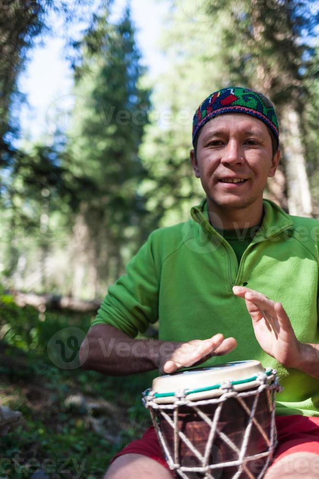 Mann, der die Handtrommeln in der Natur spielt foto