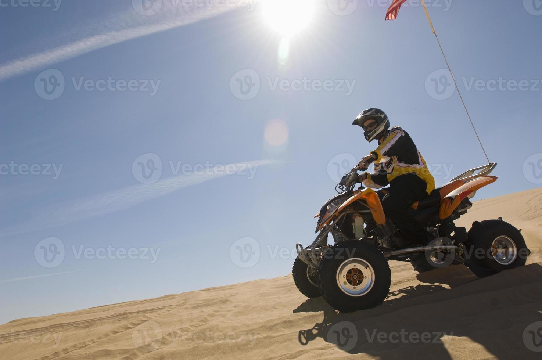 Mann, der Quadbike in der Wüste reitet foto