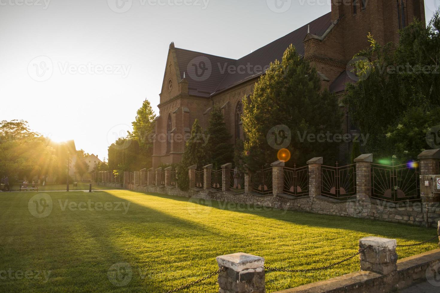 Lichtstrahl in einem grünen Park neben einer Kirche foto