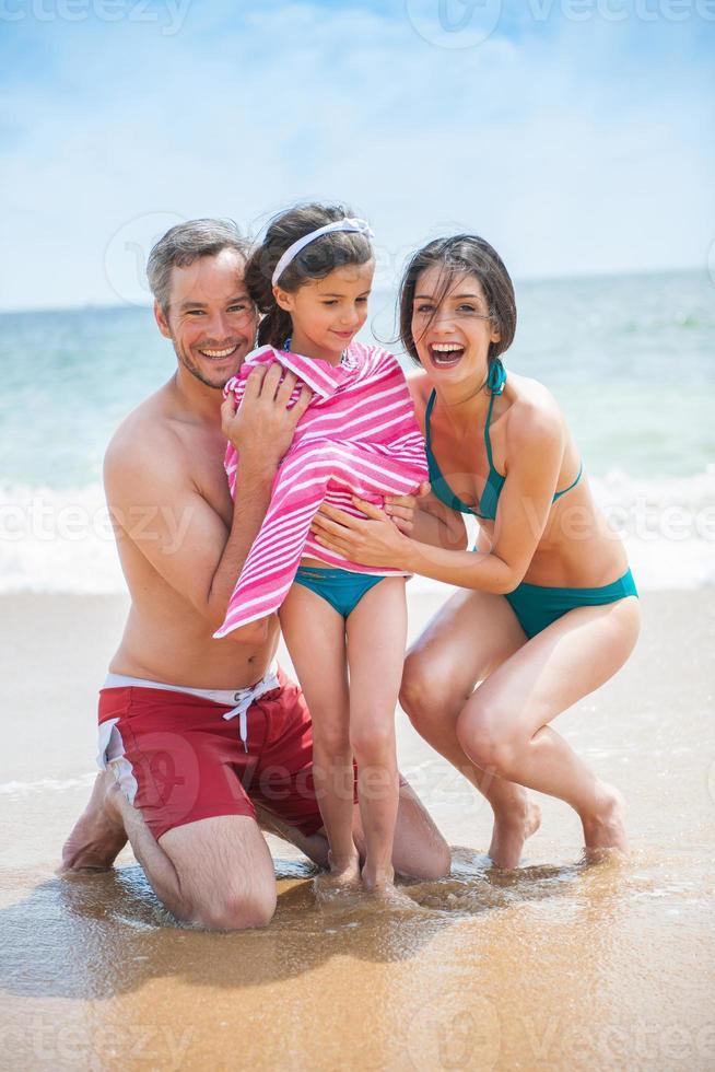Porträt eines jungen Paares in Badeanzügen mit ihrer Tochter foto