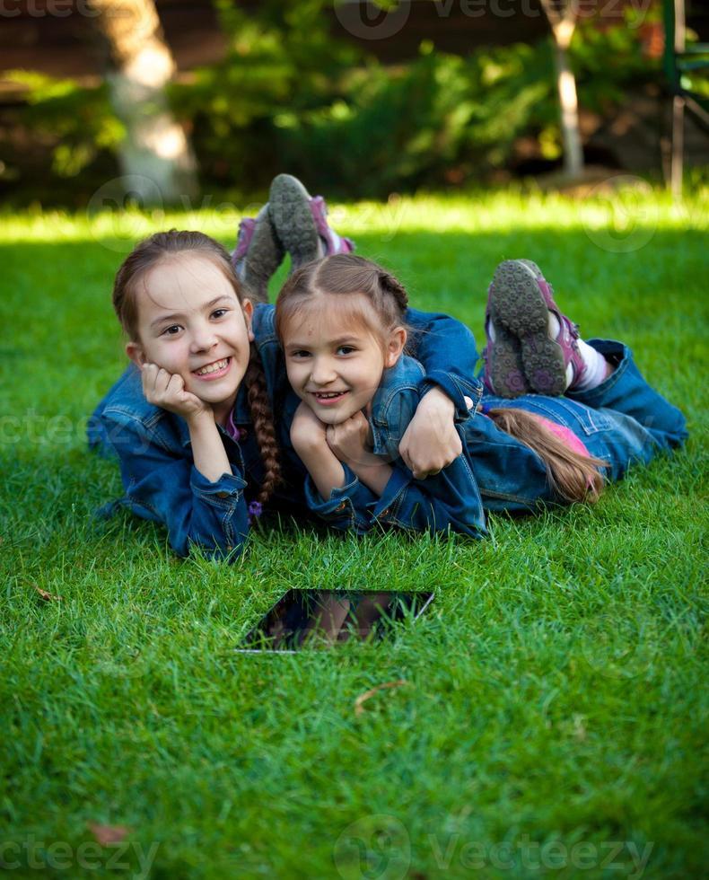 zwei Mädchen, die Spaß auf Gras mit Tablette haben foto