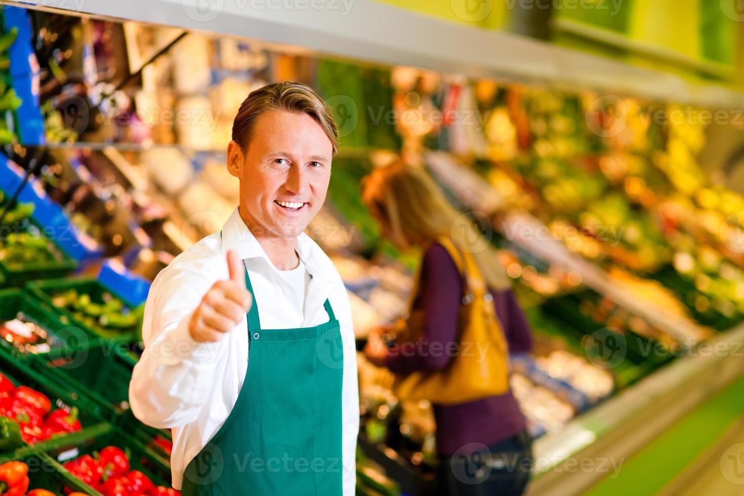 lächelnder Mann in der grünen Schürze mit einem Daumen oben im Supermarkt foto