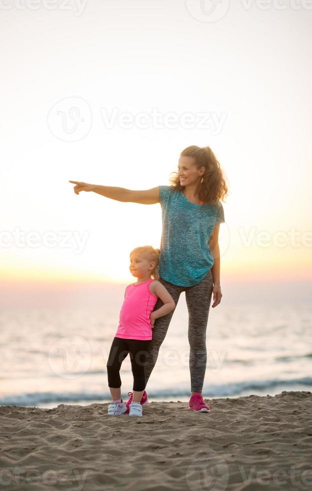 fit junge Mutter zeigt in die Ferne für Tochter am Strand foto
