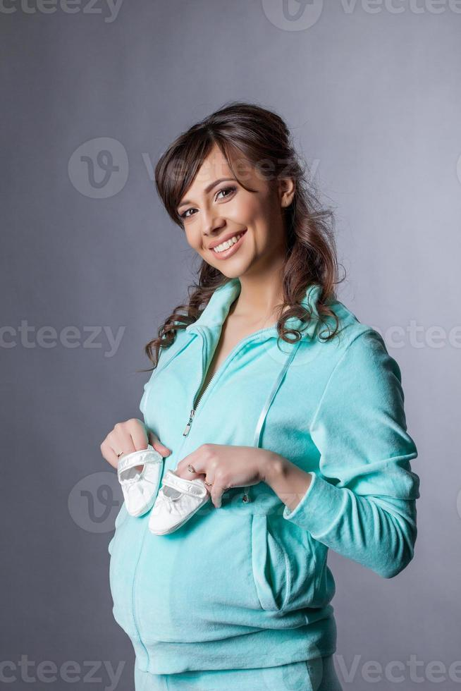 glückliche lächelnde werdende Mutter, die mit Booties aufwirft foto