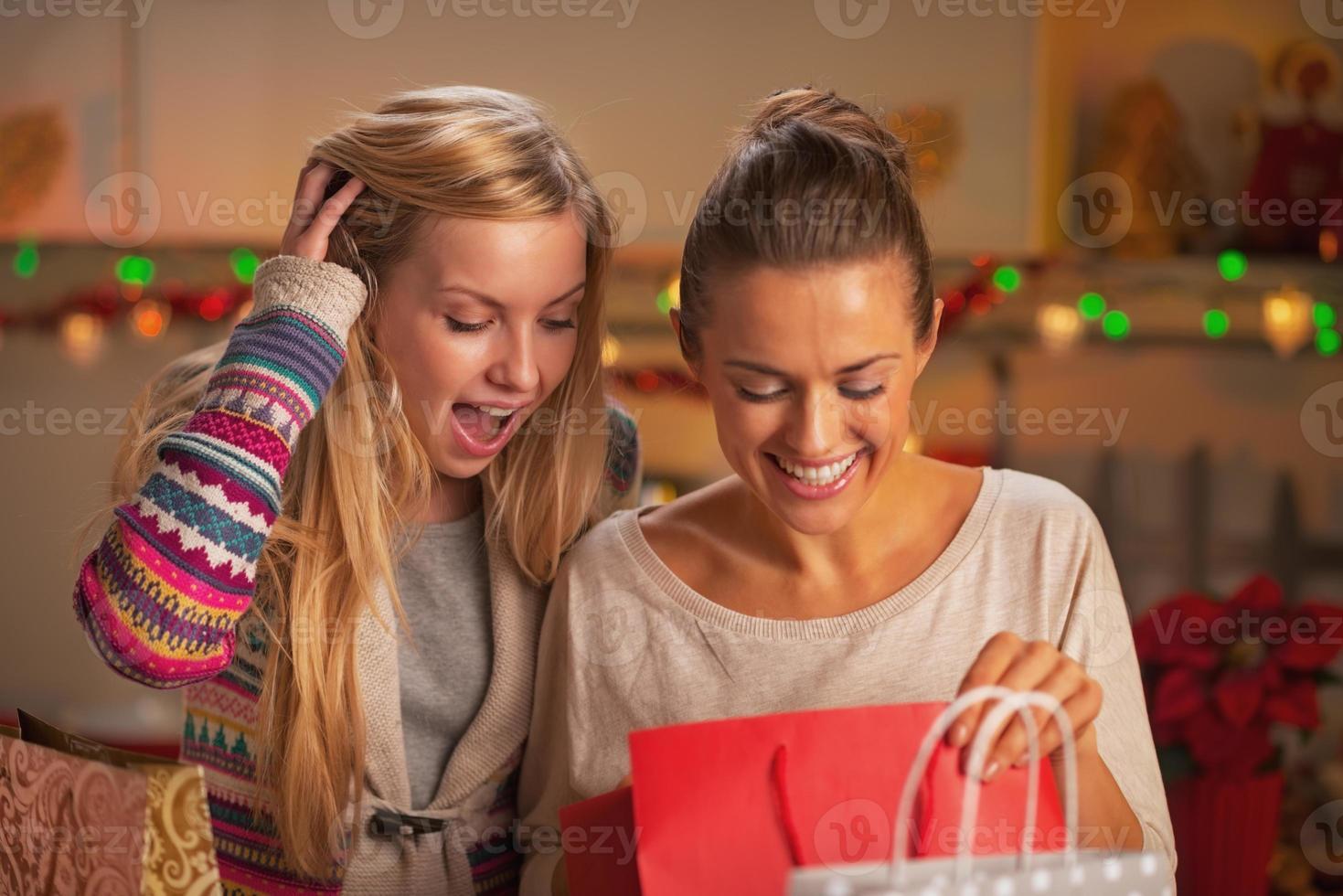 glückliche zwei Freundinnen, die Taschen nach dem Einkauf erforschen foto