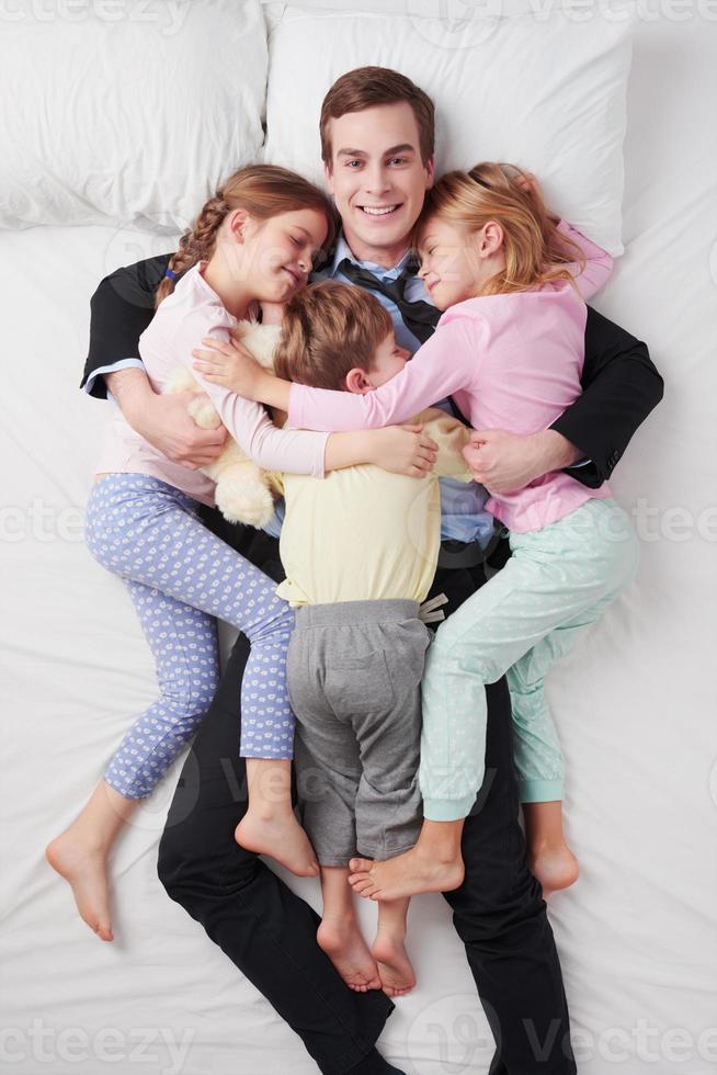 Draufsicht des lächelnden Geschäftsmannes und seiner drei Kinder foto