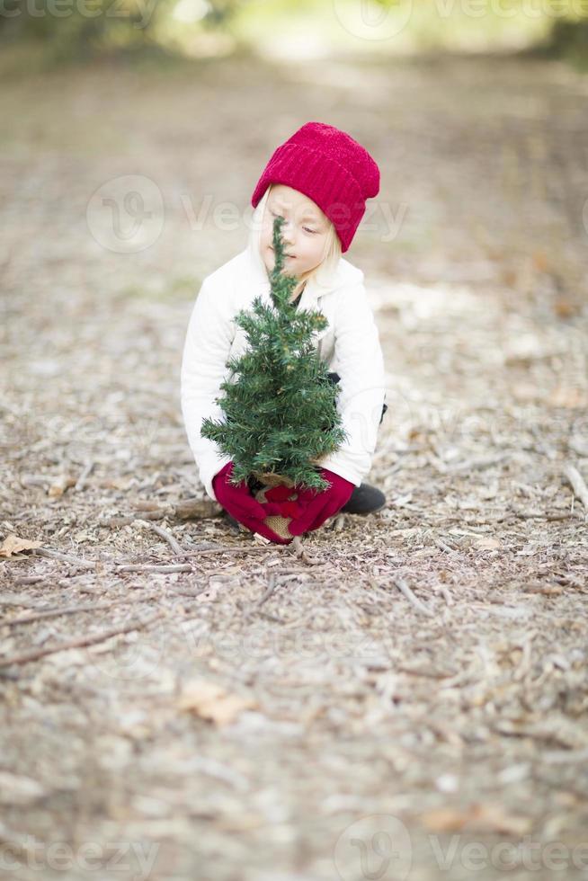 Mädchen in roten Fäustlingen und Mütze nahe kleinem Weihnachtsbaum foto