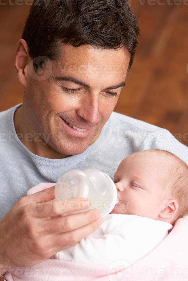 Porträt des Vaters, der Neugeborenes Baby zu Hause füttert foto