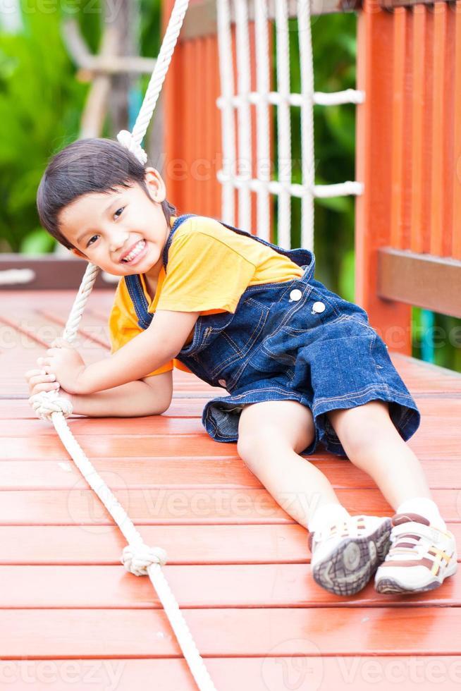 glücklicher Junge, der das Seil klettert foto