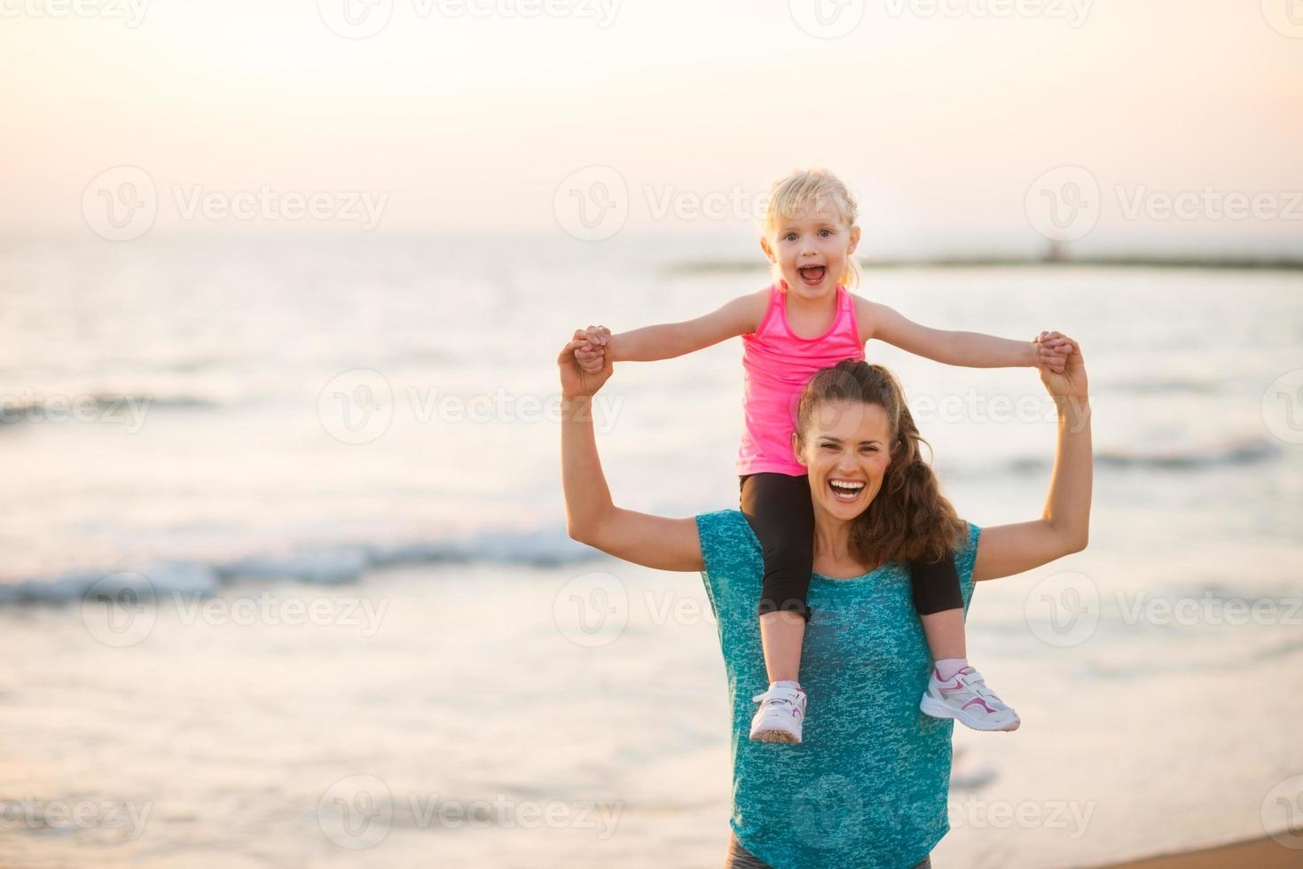 freudige Mutter, die Tochter am Strand bei Sonnenuntergang hält foto