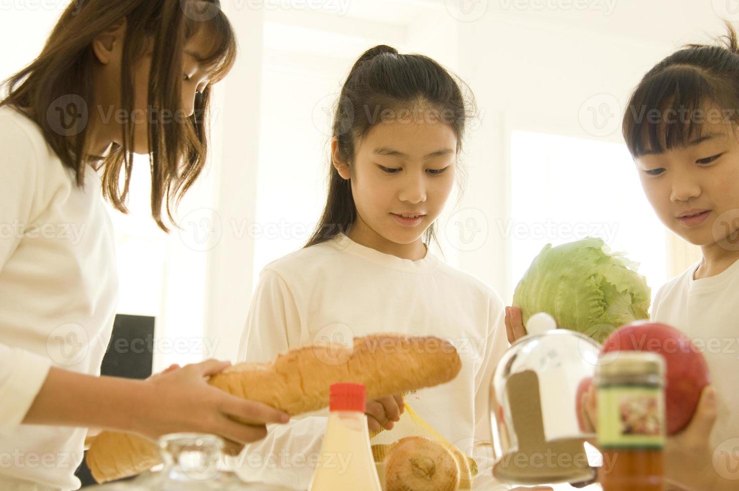 japanische Kinder bereiten sich auf das Kochen vor foto