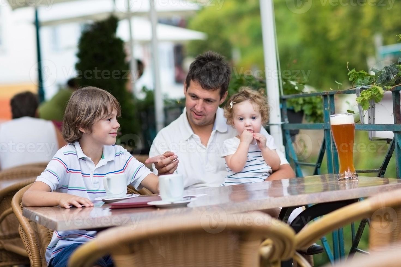 junger Vater, der mit seinen Kindern im Außencafé entspannt foto