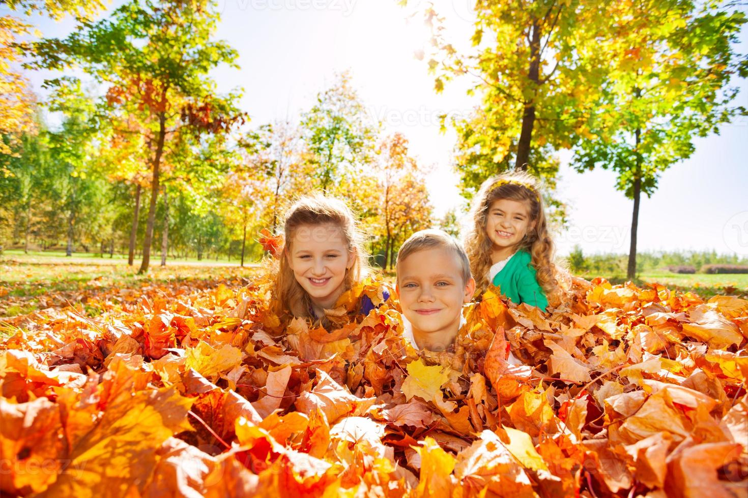 Kinder haben Spaß daran, mit Blättern auf dem Boden zu liegen foto
