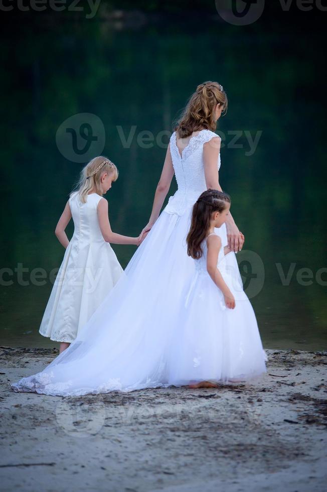 Braut führt Blumenmädchen zum Wasserrand foto