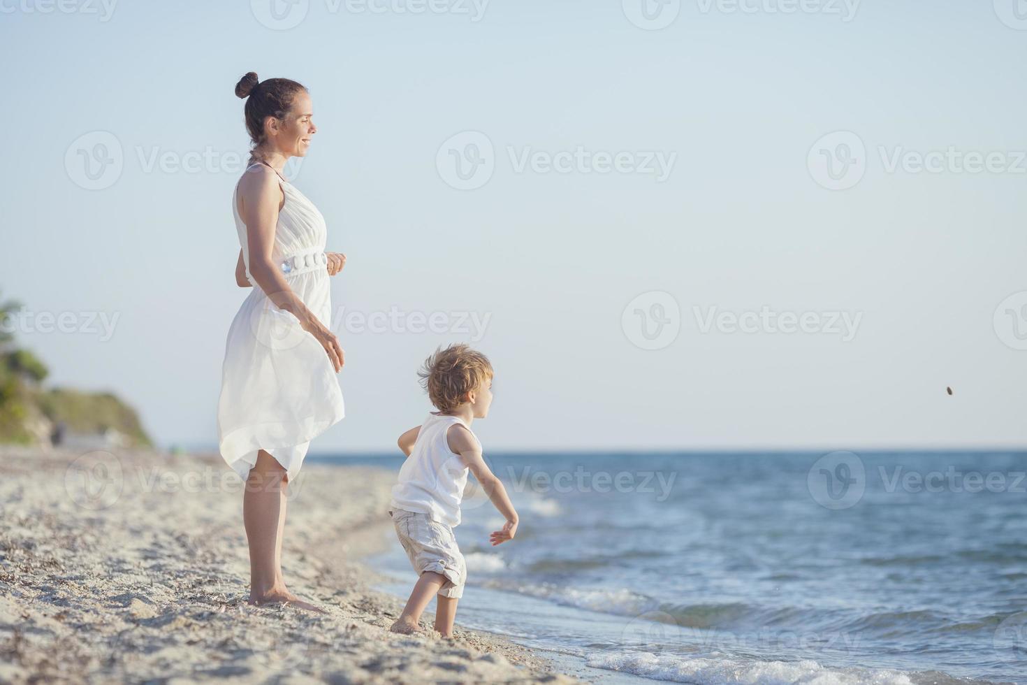 Spielen mit Skimming Steinen am Strand foto