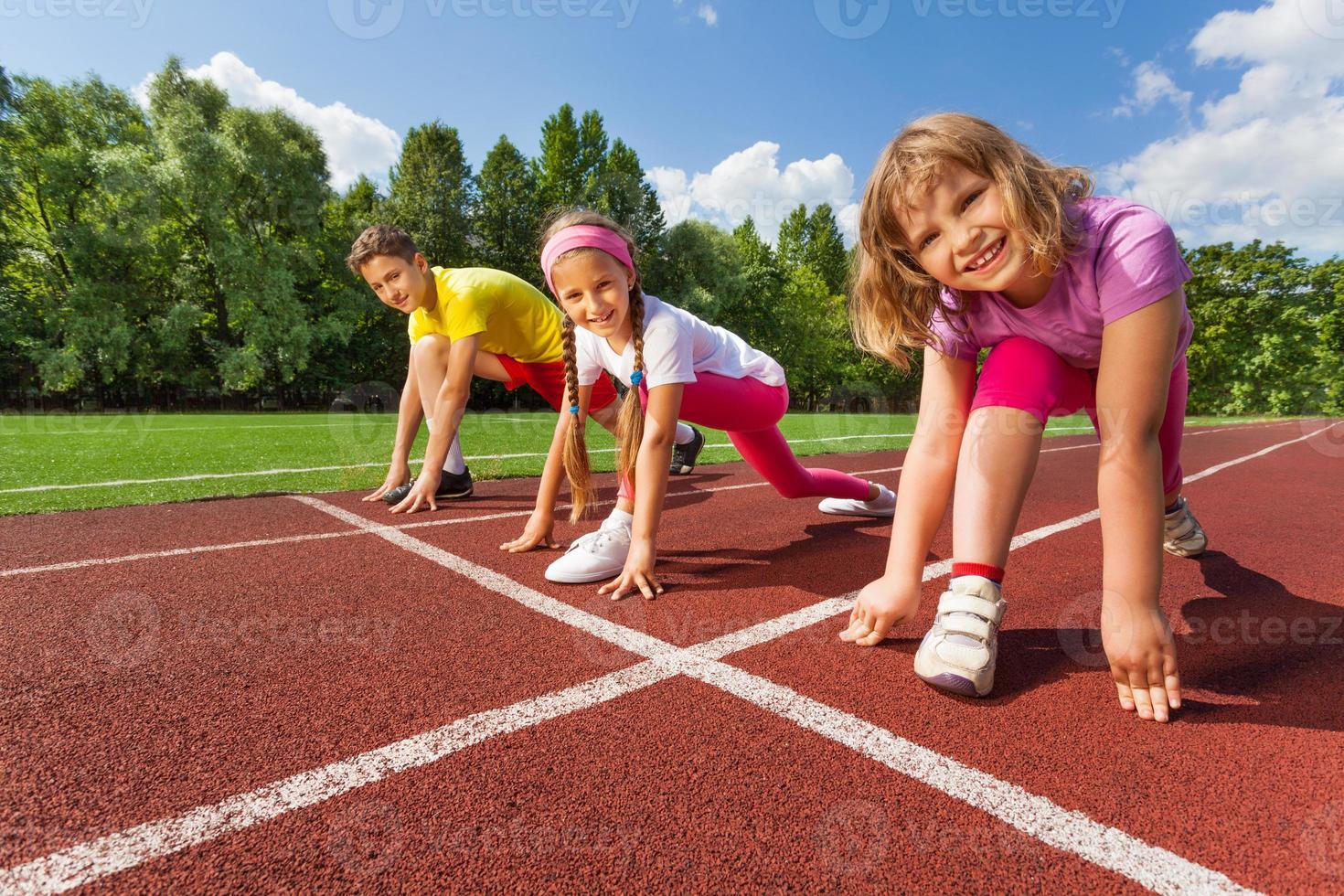 drei lächelnde Kinder in Bereitschaftsposition zu rennen foto