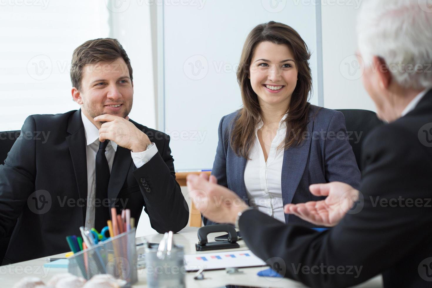 lächelnder Mann und Frau, die dem Gespräch des älteren Mannes zuhören foto