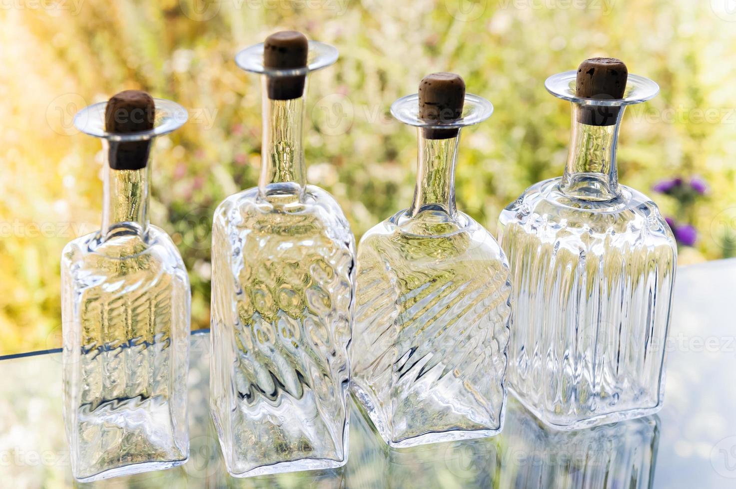 vier Flaschen mit ausgefallenem klarem Glas auf Blumenhintergrund. foto