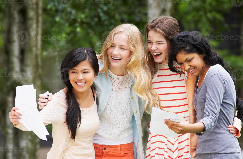 Vier Mädchen im Teenageralter feiern erfolgreiche Prüfungsergebnisse foto