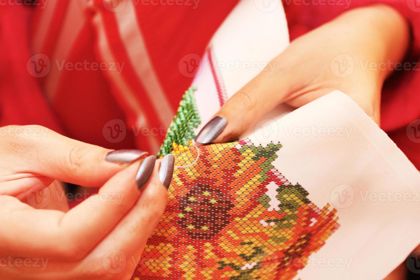 Stickprozess auf Stoffperlen Hände foto