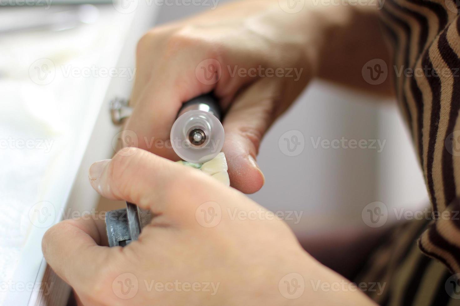 Zahntechniker bearbeitet die künstlichen Zähne mit Mikromotor foto