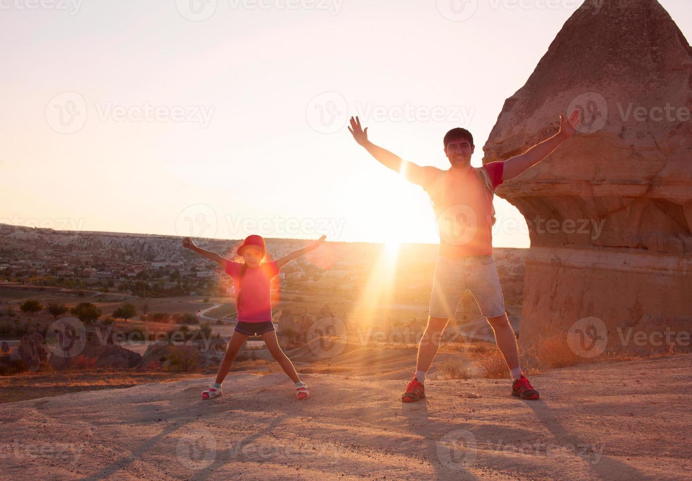 junger Mann mit der kleinen Tochter, die Sonnenuntergang auf Berggipfel trifft foto