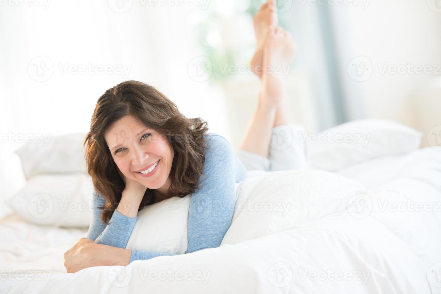 fröhliche reife Frau, die im Bett liegt foto
