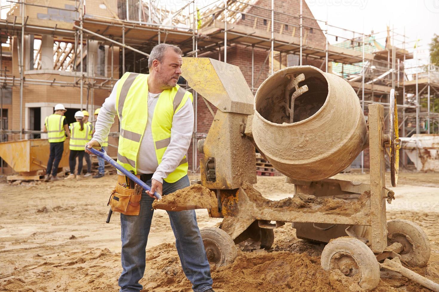 Bauarbeiter auf der Baustelle Zement mischen foto