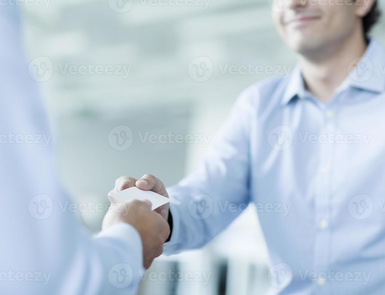 Nahaufnahme von zwei Geschäftsleuten, die Visitenkarten austauschen foto