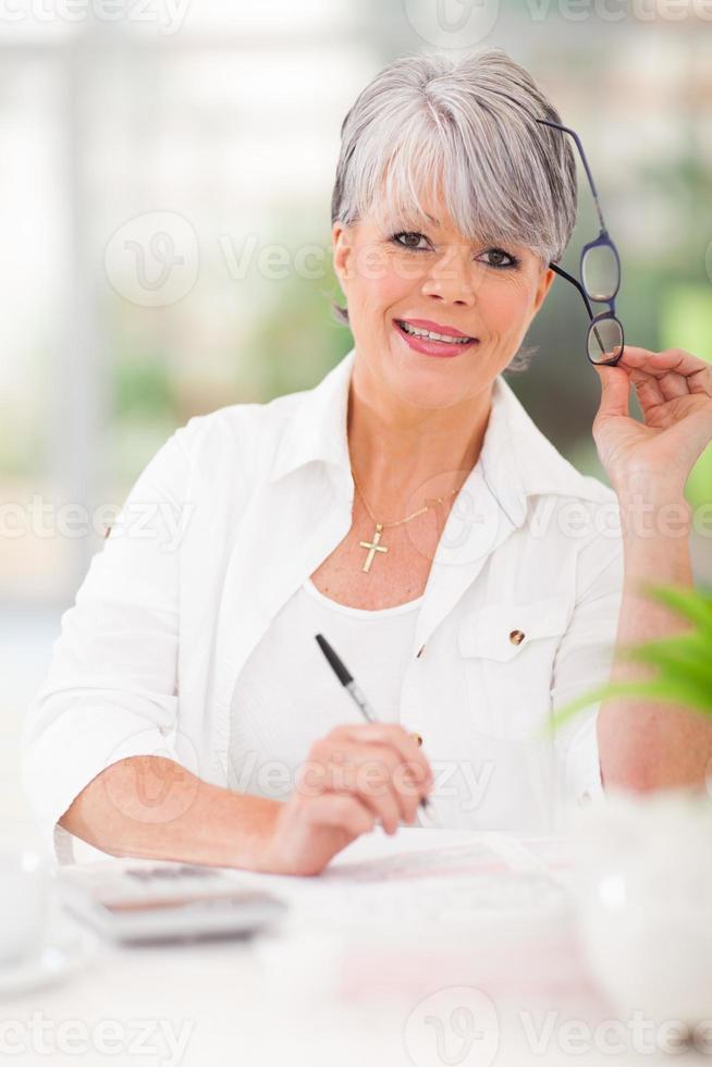 ältere Frau, die Hausfinanzen tut foto