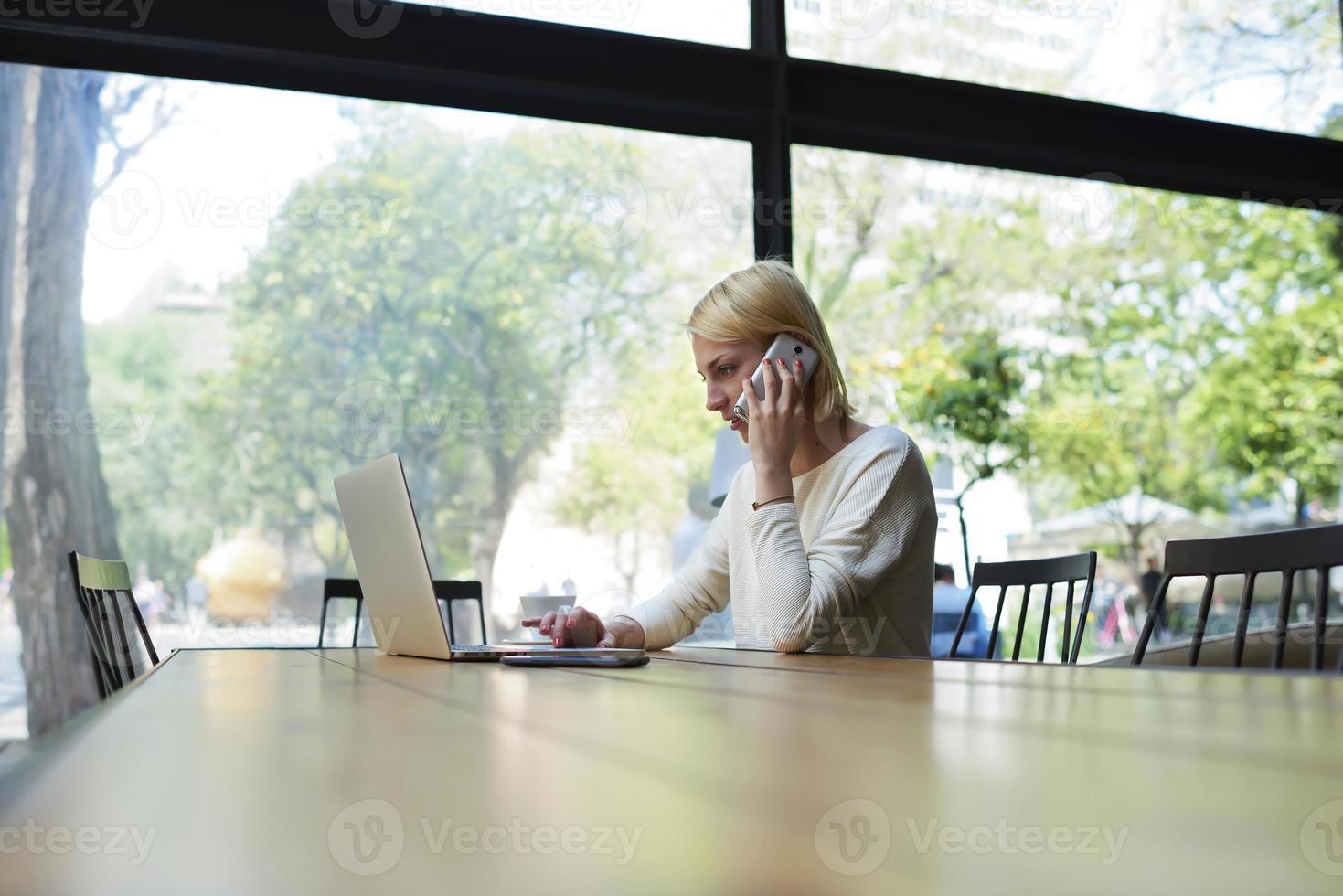 Geschäftsfrau Tastatur auf ihrem Laptop-Computer beim Sprechen auf dem Smartphone foto