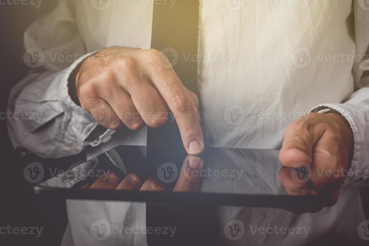 Geschäftsmann, der an digitalem Tablet-Computer arbeitet foto