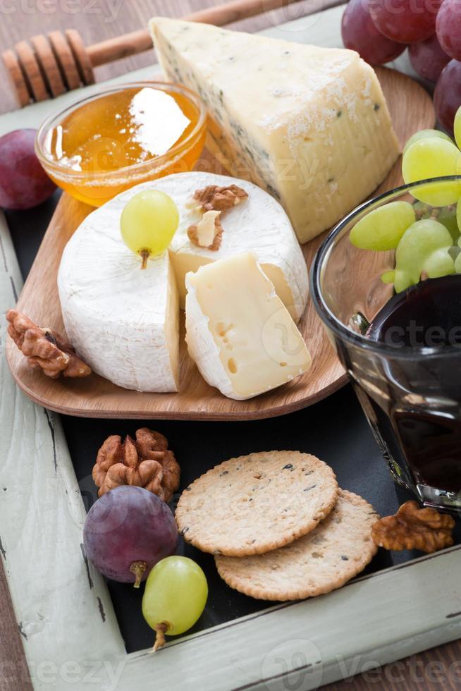 verschiedene Vorspeisen zu Rotwein - Käse, frische Trauben foto