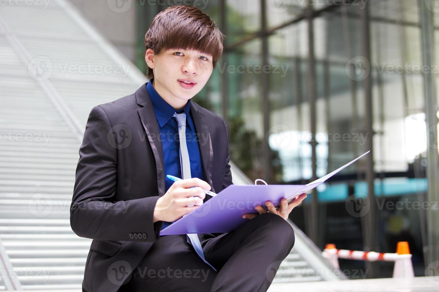 junge asiatische männliche Geschäftsführerin, die Datei hält foto
