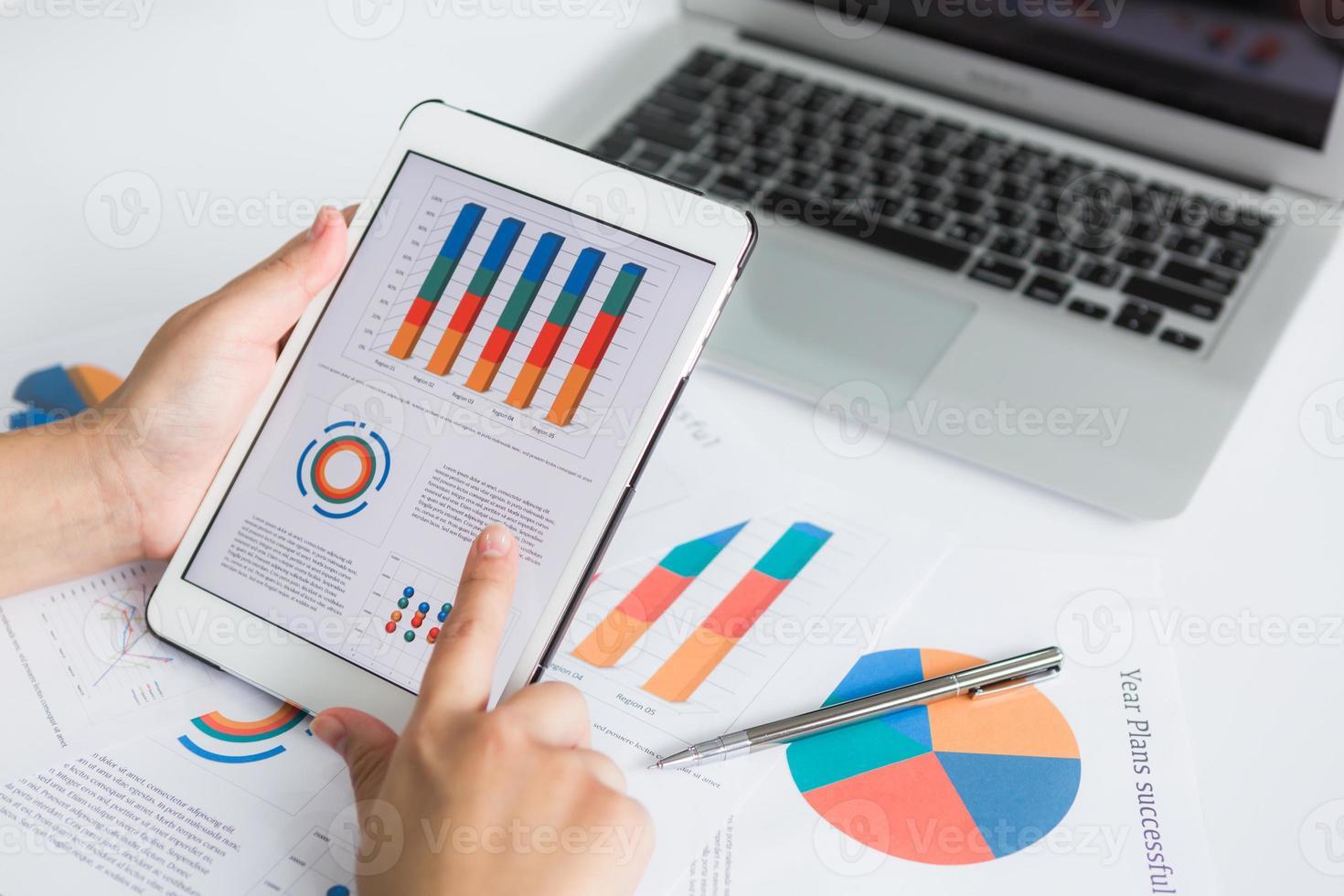 Nahaufnahme der Geschäftsperson, die digitales Tablett mit finanziellem verwendet foto