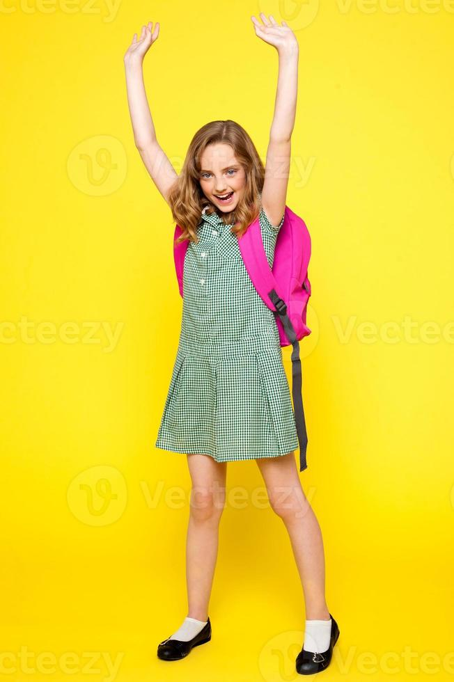 aufgeregtes Schulmädchen posiert mit erhobenen Armen foto