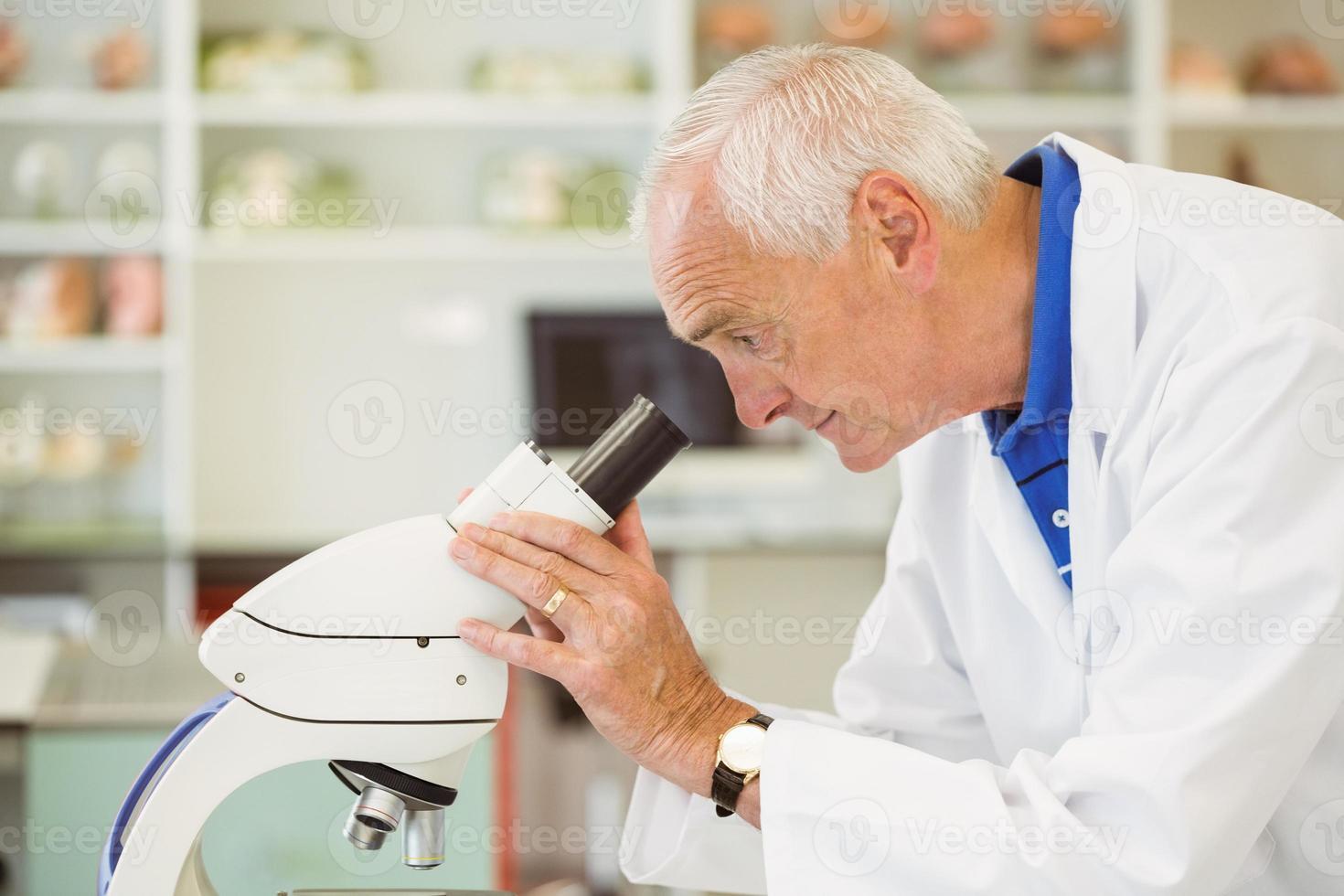 leitender Wissenschaftler, der durch Mikroskop schaut foto