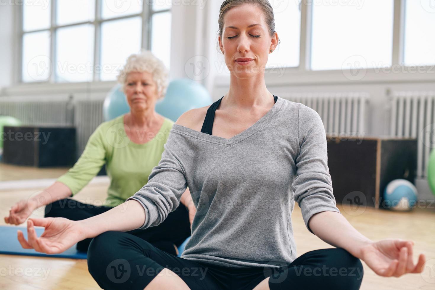 Frauen, die sich in ihrem Yoga-Kurs im Fitnessstudio entspannen und meditieren foto