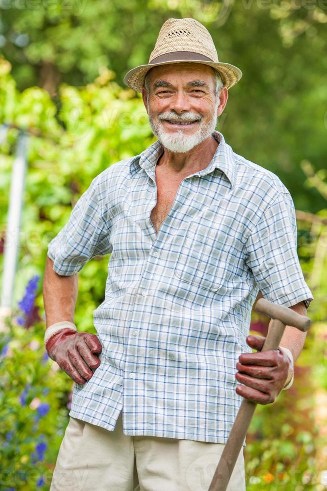 älterer Gärtner mit einem Spaten foto